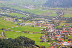 Aerial panorama of towns and highways in a valley surrounded by Alpine mountains Stock Image