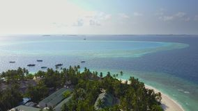 Aerial panorama view of tropical island resort hotel with white sand palm trees and turquoise Indian ocean on Maldives stock footage