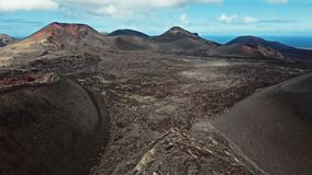 Aerial panorama of volcanic valley near Timanfaya National Park, Lanzarote. Flying over volcano near Timanfaya National Park, Lanzarote, Canary islands, Spain stock video footage