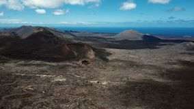 Aerial panorama of volcanic valley near Timanfaya National Park, Lanzarote. Flying over volcanos near Timanfaya National Park, Lanzarote, Canary islands, Spain stock video footage