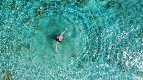 Aerial panorama on young woman dancing and turning around in blue sea stock footage