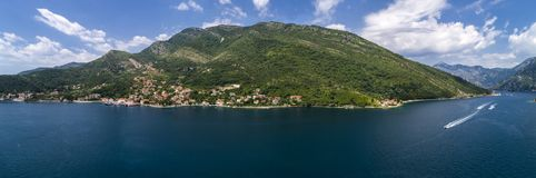 Aerial panoramic beautiful view from above to Kotor Bay and regular passenger ferry from Lepetane to Kamenari by a sunny afternoon royalty free stock image