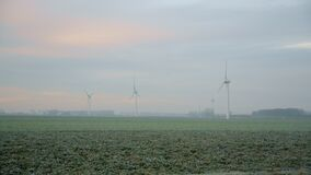 Aerial panoramic landscape of green meadow and windmills on foggy day. Amazing view on wind turbines generating energy