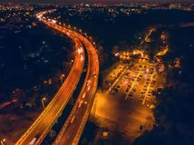 Aerial panoramic view from above to night city with bridge, road with car traffic and parking for automobiles, drone photo. Toned royalty free stock photos