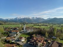 Aerial view of Bavarian village in beautiful landscape close to the alps. Aerial panoramic view of authentic Bavarian village with catholic church close to the stock photo