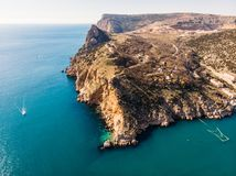 Aerial panoramic view of Balaklava bay in Crimea, mountain cliffs and sea with ships. Beautiful nature panorama landscape. Black sea coast from air, drone shot royalty free stock photography