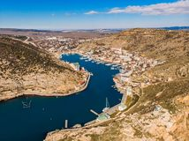 Aerial panoramic view of Balaklava bay in Crimea, mountain cliffs and sea with ships. Beautiful nature panorama landscape. Town among hills and black sea coast royalty free stock photos