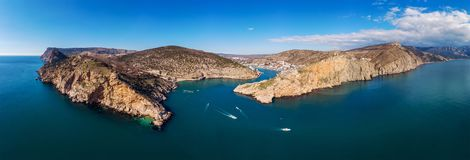 Aerial panoramic view of Balaklava bay in Crimea, mountain cliffs and sea with ships. Beautiful nature panorama landscape. Town among hills and black sea coast stock photos