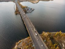 Aerial panoramic view of big river and transportation bridge over it with cars in autumn European city.  stock photo