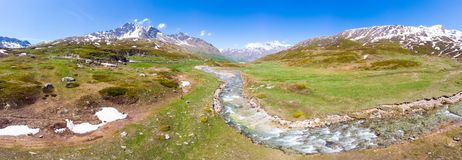 Aerial panoramic view of high mountain peaks in the Alps. Stream flowing amid meadows in spring season. Idyllic scenery, clear royalty free stock photography