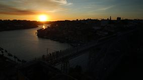 Porto train at sunset. Aerial panoramic view of Oporto train at sunset crossing Dom Luis I Bridge at twilight. Picturesque urban cityscape of Porto, Portugal stock video
