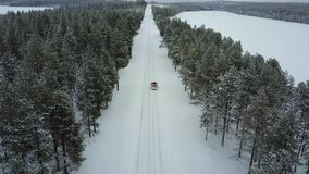 Aerial panoramic view of the only red car on the road in the beautiful winter landscape of Lapland during a snowfall. Tracking a retiring car. Aerial 4K video stock footage