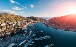 Aerial panoramic view of sunset over Balaklava, Crimea sea bay with many yachts and boats in resort coast between mountains. Beautiful tourist luxury European stock images