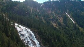 Aerial panoramic view of a waterfall on the pine forests and with sunlights in the mountains in Austria. Aerial panoramic view of a waterfall on the pine stock video
