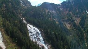Aerial panoramic view of a waterfall on the pine forests and with sunlights in the mountains stock video footage