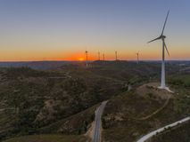 Aerial panoramic Wind farm turbines silhouette at sunset. Clean renewable energy power generating windmills. Algarve countryside. Portugal Royalty Free Stock Image
