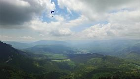 Aerial paragliding over mountains and valleys stock footage