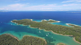 Aerial: peninsula with clear blue ocean water Nautical vessels anchored in a bay stock video