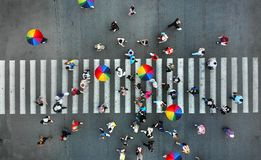 Aerial. People crowd on a pedestrian crossing crosswalk. View above stock image