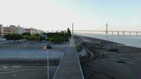 Aerial from people sporting at the Vasco da Gama Bridge in Lisbon Portugal stock video footage