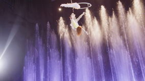 Aerial performer making acrobatic act against colorful fountains, acrobatics, Moscow, Russia stock video