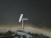 Aerial Photo of a Boat docked at a Small Jetty. Drone aerial photograph of a boat docked at a small jetty, with blackened waters due to a nearby shipyard causing royalty free stock image