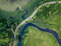 Aerial Photo of Car Driving on the Road going by the River under the Trees, Top Down View in Early Spring on Sunny Day stock photos