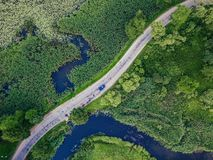 Aerial Photo of Car Driving on the Road going by the River under the Trees, Top Down View in Early Spring on Sunny Day stock images