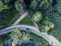 Aerial Photo of Car Driving on the Road going by the River under the Trees, Top Down View in Early Spring on Sunny Day - Concept. Drone Photo of Car Driving on stock photos