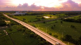 Aerial Photo Countryside Car Running on Road Bridge Over Railway. Bypass route the City and Golden Hour Sky Beautiful Landscape Drone View Stock Photo