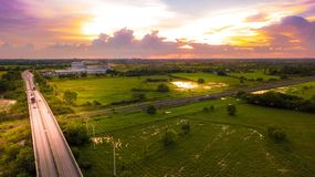 Aerial Photo Countryside Car Running on Road Bridge Over Railway. Bypass route the City and Golden Hour Sky Beautiful Landscape Drone View Stock Photography