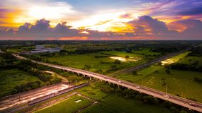 Aerial Photo Countryside Road Bridge Over Railway The train is r. Unning through the bridge and Golden Hour Sky Beautiful Landscape Drone View Royalty Free Stock Photography