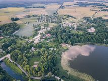 Aerial Photo of Countryside Village Between Trees and with Big Blue Lake Besides it in Early Spring on Sunny Day - Concept of. Peaceful Life in Countryside in royalty free stock image