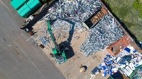 Crane with a huge claw in front of a steel scrap heap stock images