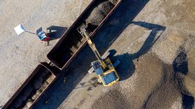Aerial photo of an excavator loading a wagon with gravel stock photo
