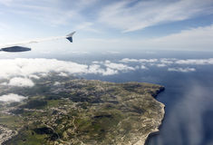 Aerial photo of the island landscape with clouds view on the sea stretching all the way to the horizon Stock Photos