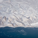 Aerial photo of lake edge and moutainous region. Covered in snow and ice Royalty Free Stock Photos
