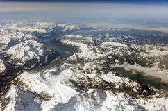 Aerial photo of the landscape with clouds, snowy mountains and view stretching all the way to the horizon Stock Image