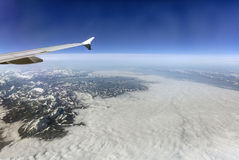 Aerial photo of the landscape with clouds, snowy mountains and view stretching all the way to the horizon Stock Photo