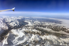 Aerial photo of the landscape with clouds, snowy mountains and view stretching all the way to the horizon Royalty Free Stock Images