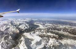 Aerial photo of the landscape with clouds, snowy mountains and view stretching all the way to the horizon Royalty Free Stock Image