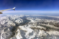 Aerial photo of the landscape with clouds, snowy mountains and view stretching all the way to the horizon Royalty Free Stock Photo