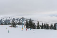 Skiers and snowboarders going down slopes of Whistler Blackcomb Royalty Free Stock Image