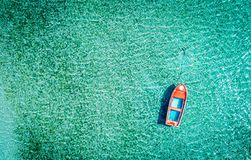 Aerial photo of motorboat tied up in turquoise sea water, Greece. Aerial photo of a red lonely tboat tied up in crystal clear turquoise sea water royalty free stock image