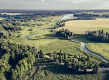 Aerial Photo the River Flowing Between Yellow and Green Agriculture Fields in Early Spring on Sunny Day - Concept of Peaceful Life. In Countryside in Harmony royalty free stock photography