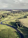 Aerial Photo the River Flowing Between Yellow and Green Agriculture Fields in Early Spring on Sunny Day - Concept of Peaceful Life. In Countryside in Harmony royalty free stock image