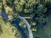 Aerial Photo of Road going by the River under the Trees, Top Down View in Early Spring on Sunny Day - Concept of Peaceful Life in. Countryside in Harmony stock images