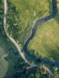 Aerial Photo of Road going by the River under the Trees, Top Down View in Early Spring on Sunny Day - Concept of Peaceful Life in. Countryside in Harmony royalty free stock images