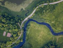 Aerial Photo of Road going by the River under the Trees, Top Down View in Early Spring on Sunny Day - Concept of Peaceful Life in. Countryside in Harmony stock image