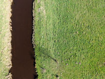 Aerial photo of a small river by meadows, abstract photo. Abstract aerial photo, more darkly small river in the left image border, on the right green meadows Royalty Free Stock Photo